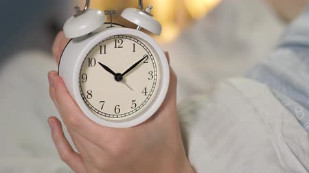 zegar : Female hands holding alarm clock and set small hand for six hours. Close-up