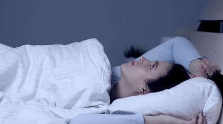 deprivation : Girl can not fall asleep. Insomnia noisy neighbors concept. Young attractive caucasian girl lies alone in bed under covers and looks at ceiling. Medium shot Stock Footage