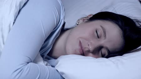tür : Girl sleeping and smiling. Sweet dreams concept. Young attractive caucasian girl sleeps alone in bed hugging pillow and experiences positive emotions. Close-up
