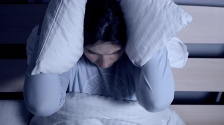 irritação : Noisy neighbors concept. Young attractive girl sits on bed covering her ears with pillow. Close-up