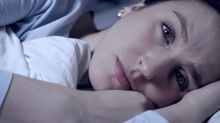Girl is crying at night. Resentment, frustration, problems in personal life, problems in relationships concept. Attractive woman lies in bed looking at camera and tears flow down her face. Close-up