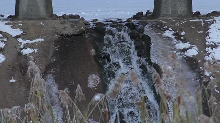 Little waterfall under the bridge at winter wather, close-up an slowmo