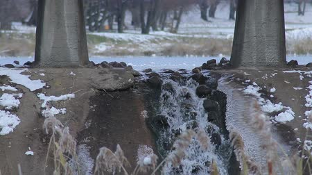 Little waterfall under the bridge on the background of lake at winter wather Wideo