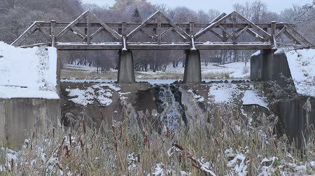Little waterfall under the bridge on the background of lake and some snowfall