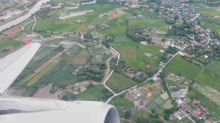 Airplane or aircraft take off from runway. See airplane wing and engine on aerial view green landscape background. Stock Footage