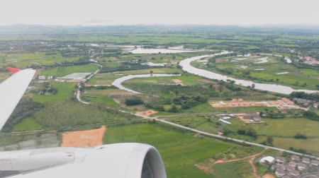 Airplane or aircraft take off from runway. See airplane wing and engine on high angle view green landscape background.