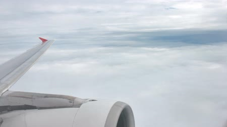 Aerial view of airplane flying wing and engine on sky and white cloud. Atmosphere or aircraft outside