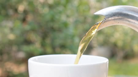Hot tea pouring into white tea cup close-up view on green leaves of tree background. Good healthy and slow life concept Stock Footage