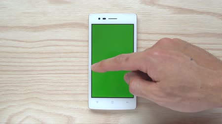 Human is sliding Smartphone or Mobile Phone green screen on wood background 4k 3840x2160 hi resolution. Technology usage. Touching green screen of Smartphone.