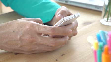 Green t-shirt businessman typing or chat play smartphone close up view. Small business SME or startup human is contacting or communicate with customer. Hi resolution 4K 3840x2160 footage. Stock Footage