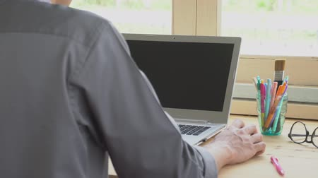 Gray shirt businessman click mouse or working in front of laptop. Small business SME or startup concept. Internet connection and communication style. Hi resolution footage 4K 3840x2160