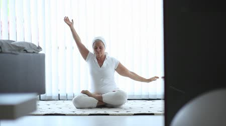 eyes closed : Senior woman doing yoga, sitting in lotus position: Full HD