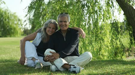 retirement : Happy senior couple sitting under a willow tree