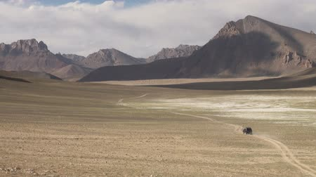 pamirs : A jeep drives through a spectacular mountain region in the Pamir ranges.