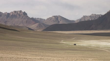 poros : A jeep drives through a spectacular mountain region in the Pamir ranges.