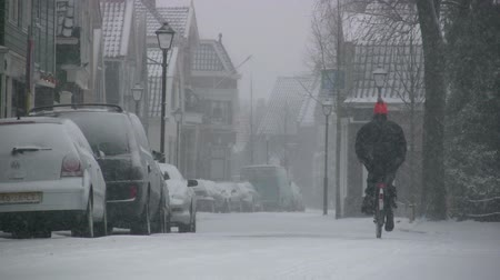 rüzgârla oluşan kar yığını : A man cycles through a snow storm in a Dutch village.