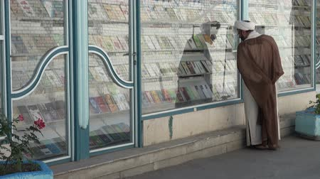 bookshop : An Iranian mullah looks at books in a religious bookstore.