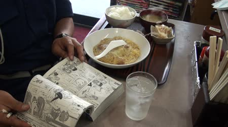 cômico : A man reads a Japanese comic book while having lunch. Vídeos
