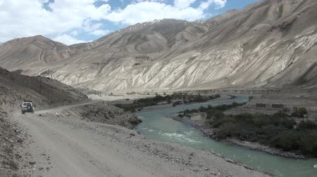 pamirs : A jeep drives through spectacular mountain scenery in the Pamir ranges. Stock Footage