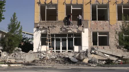 azbest : Men are taking down an old Soviet apartment building.