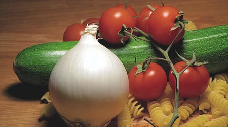 tomate cereja : Onion zucchini cherry tomatoes pasta on wooden cutting board