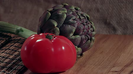 saborear : Raw tomatoes with artichoke placemat on a wooden chopping board