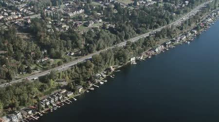 ипотека : Low-flying view along highway and lakeside waterfront houses and docks Стоковые видеозаписи