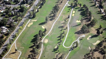 поле для гольфа : Right panning aerial view of golf course and country club on sunny, warm day