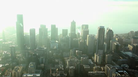 Sun rays across tall buildings downtown on smoggy, sunny afternoon