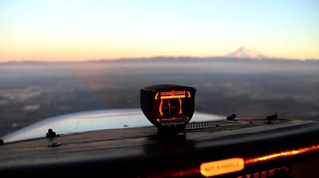 Pilots point of view of switching focus from compass instrument in foreground to mountain in background