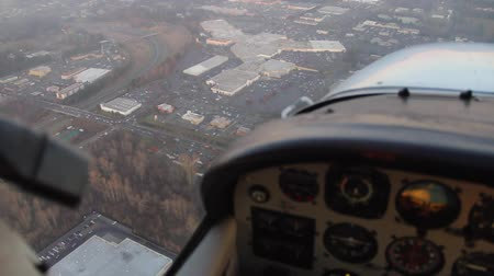 pilótafülke : View of malls and highways from low-flying small airplane with instrument panel in foreground Stock mozgókép