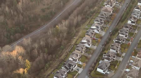 neighbor : Low-flying view following road around a hillside bend in residential area