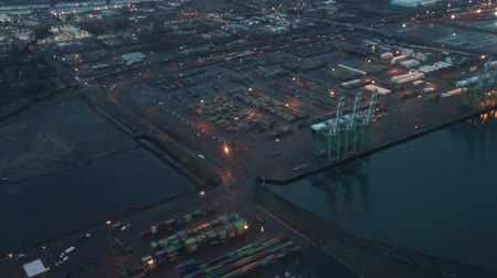 Panning overhead perspective over freight docks on rainy night