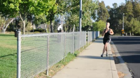 aerobic : A young woman in black jogs while outside Wideo