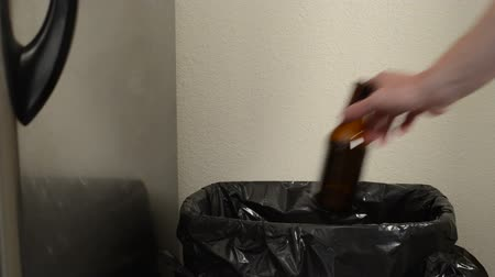 lixeira : Person throws away beer bottle, no lid on trash