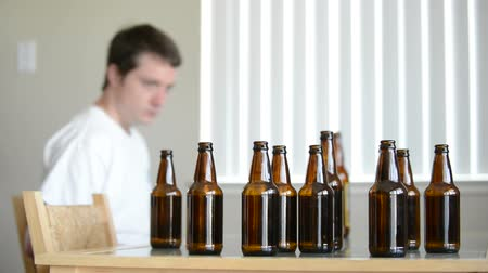 alkol : Drunk man leaves table of empty beer bottles