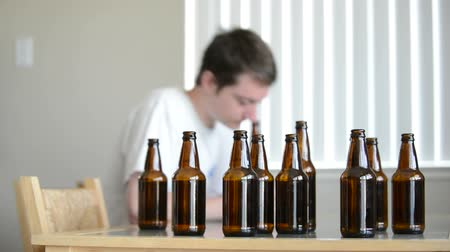 алкоголизм : Drunk man looks for more beer in empty bottles