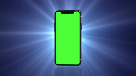 Smartphone turns on with green screen. Seamlessly loopable. Dark background with spinning flare. Easily customizable chroma key