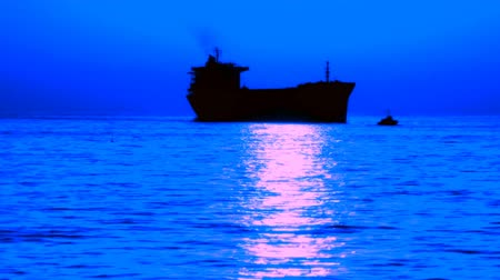 mehtap : silhouette of the cargo ship in the background of moonlight on the sea