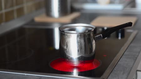 konvice : Coffee pot on cooking plate with boiling water in. Making turkish coffee.
