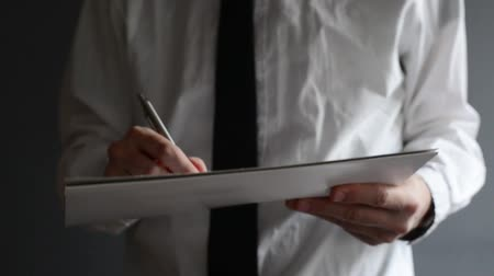 synopsis : Businessman writing or signing project documentation. Close up with selective focus. Business situation.