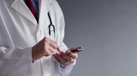 male : Male doctor in white coat is using a modern smartphone device with touch screen