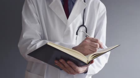 physicians : Male doctor writing prescription while standing. Health care professional writing.