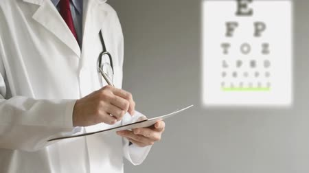 vision correction : Male ophthalmologist doctor writing prescription to patient after eye examination. Stock Footage