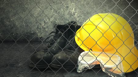 védősisak : Construction helmet and industry safety equipment. Yellow hardhat, black boots and plastic protective goggles. Stock mozgókép