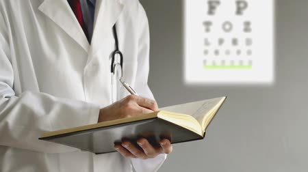 okulista : Male ophthalmologist doctor writing prescription to patient after eye examination. Wideo