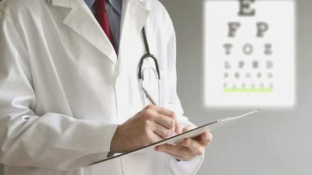 optyk : Male ophthalmologist doctor writing prescription to patient after eye examination. Wideo