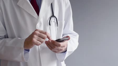 moderní : Male doctor in white coat is using a modern smartphone device with touch screen