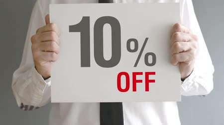 znak : Salesman holding sale tag with ten percent sales discount price. Consumerism concept, retail store promotion.