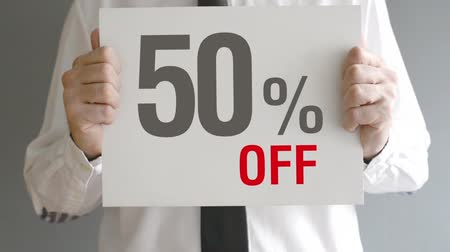 holding : Salesman holding sale tag with fifty percent sales discount price. Consumerism concept, retail store promotion. Stock Footage